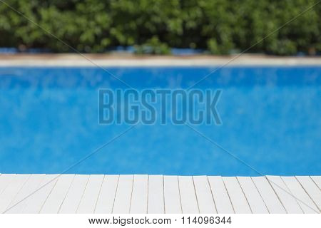 Wooden table mat with swimming pool and bushes in the background