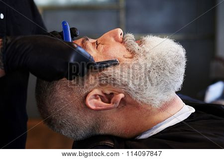 portrait of senior man in barbershop. barber shaving man with straight razor