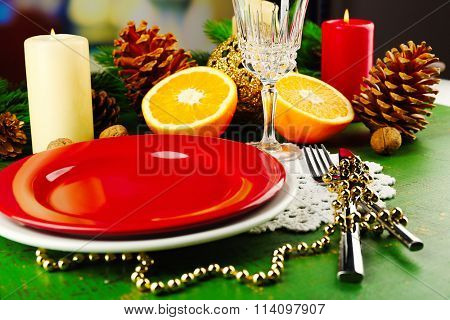Table appointments with pieces of orange and Christmas decoration background