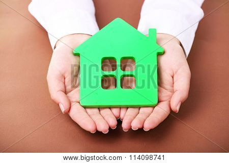 Female hands holding house on brown background