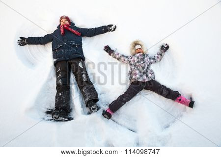 Happy boy and girl  having fun together lying in a snow making snow angels