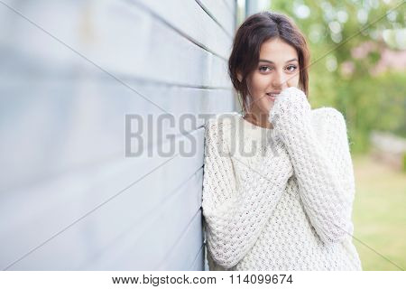 Beautiful natural young smiling shy brunette woman wearing knitted sweater by the house. Fall and winter fashion concept.