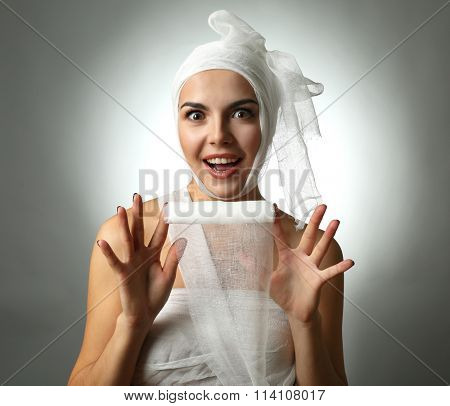 Young emotional woman with a gauze bandage on her head and chest, on grey background