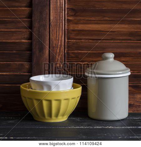 Rustic Kitchen Still Life. Vintage Ceramic Bowl And Enameled Jar On Dark Wooden Table