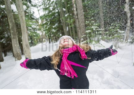 Little Girl Playing with Snow Outdoors in Winter