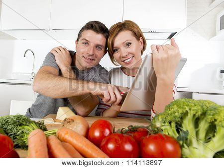 American Couple In Domestic Kitchen Wife Following Recipe In Digital Pad Working Together With Husba