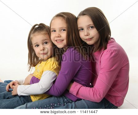 Three Sisters Sitting Down Hugging Each Other