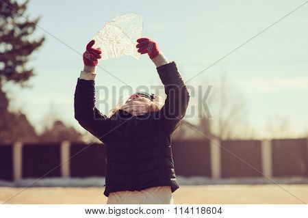 child girl exploring nature and playing with block of ice outdoor on early spring walk