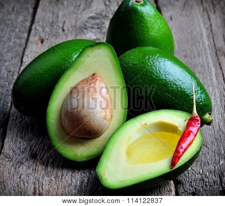 Fresh avocado with olive oil and chili pepper on a wooden background
