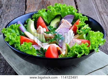 Healthy salad of avocado, tomatoes, canned tuna, onions and lettuce with parmesan, parsley and olive