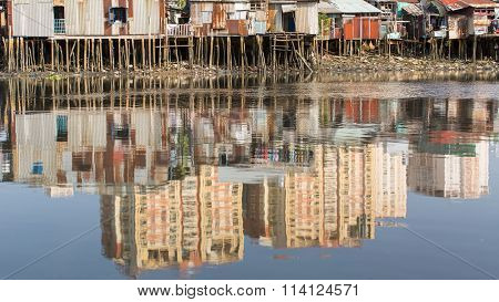 Views of the city's Slums from river - in water reflection of the new high-rise buildings. Ho Chi Minh City.