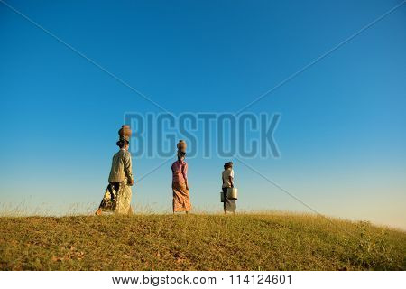 Group of Asian traditional farmers carrying clay pots on head going back home, Bagan, Myanmar