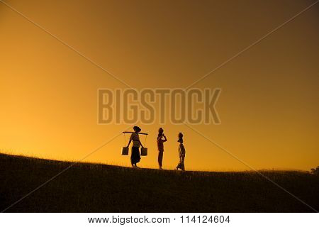 Silhouette of group Asian traditional farmers carrying clay pots on head going back home, Bagan, Myanmar
