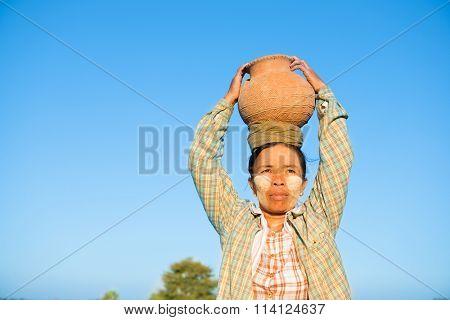 Portrait of mature Asian Burmese traditional female farmer carrying clay pot on head, Bagan, Myanmar