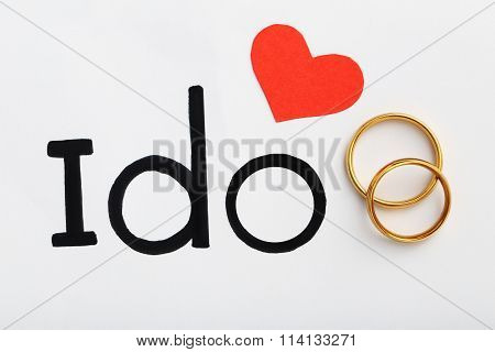 Golden Wedding Rings With Red Heart And Words I Do