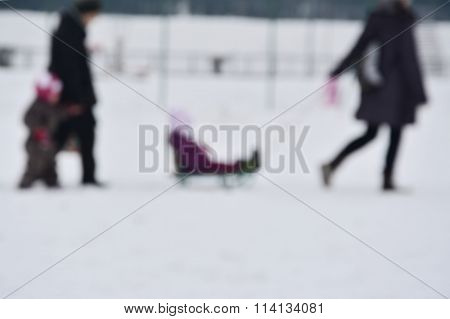 Parents With Two Children Sledding On The Snow Defocused Winter Background.