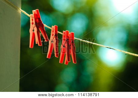 Red Clothes Pegs On String Outdoor.