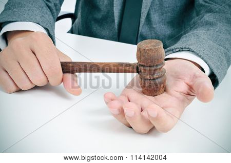 closeup of a young caucasian man in suit sitting in a desk with a wooden gavel in his hand