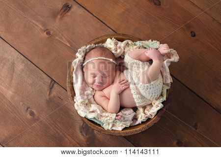 Smiling Newborn Girl Sleeping In A Wooden Bowl