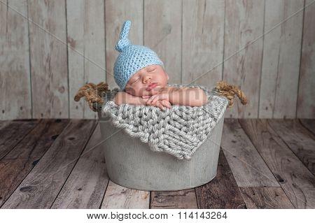 Newborn Baby Boy Sleeping In A Bucket