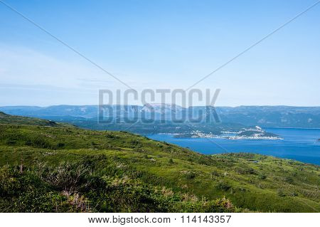 Green Hills Near Water Against Plateau Under Pale Blue Sky