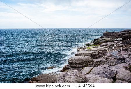 Horizon And Rocky Coastline With Waves Splashing Under Cloudy Sky
