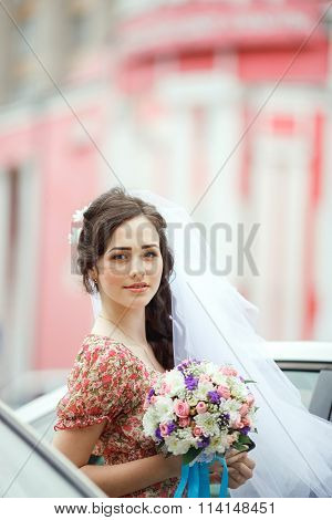 The bride in simple retro dress with floral pattern, already wearing veil, holding wedding bouquet,