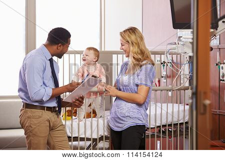 Pediatrician Visiting Mother And Child In Hospital Bed