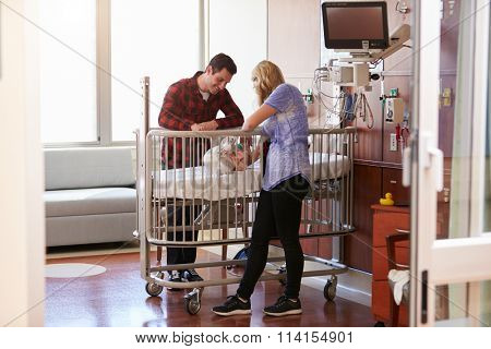 Parents With Daughter In Hospital Pediatric Unit