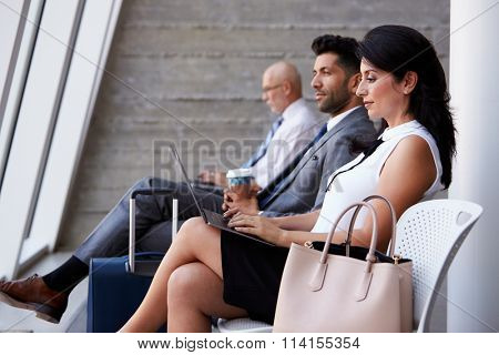Businesswoman Using Laptop In Airport Departure Lounge