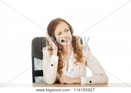 Irritated call center woman by a desk.