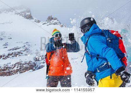 Friends playing snowballs in winter mountains