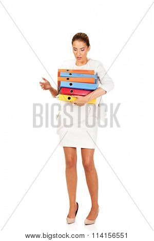 Tired businesswoman carrying heavy binders