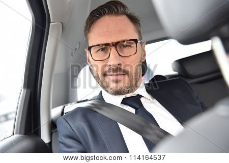Portrait of businessman sitting in taxi cab