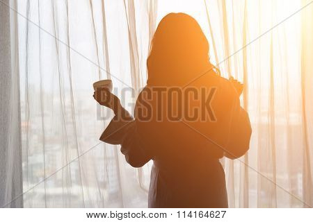 Silhouette of a woman standing in front of a window and holding a cup of coffee.