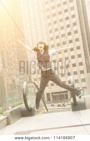 Business woman jump and excited in outside of modern city.