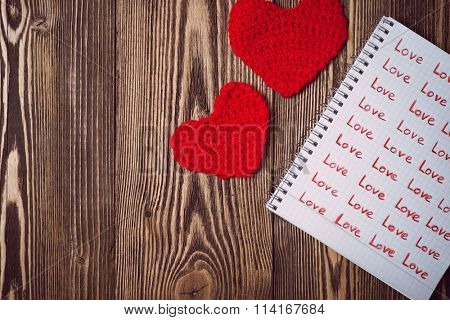 Love letter written in copybook and red knitting hearts over wooden background