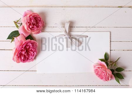 Pastel Roses  And Empty Tag  On White  Wooden Background.