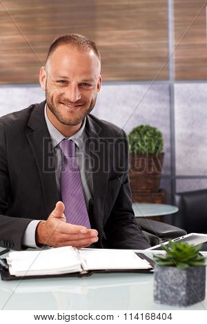 Confident businessman sitting at desk, working, having personal organizer, smiling happy, gesturing by hand.