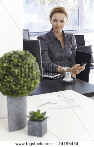 Portrait of young businesswoman sitting at desk using mobilephone, looking away, smiling.