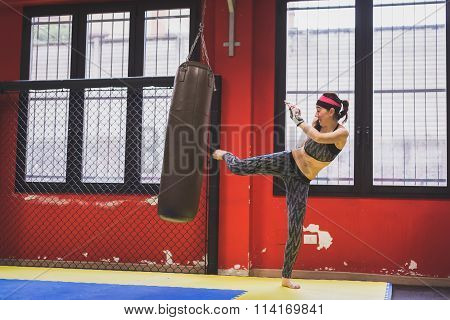 Beautiful Girl Boxing Against Punching Bag