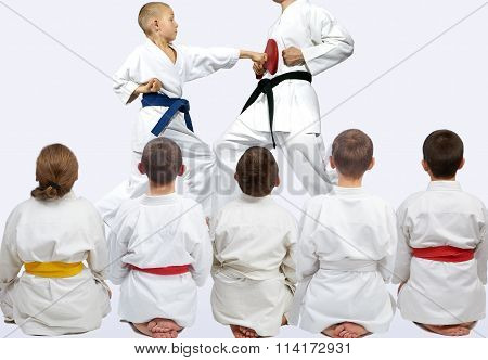 Five athletes sitting in pose looking at demonstration punch karate