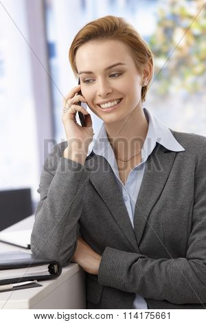 Happy young attractive businesswoman talking on mobilephone, smiling, looking down.