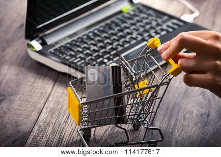 Hands pushing supermarket trolleys filled with credit hard