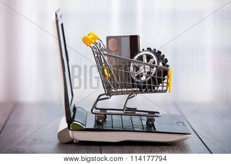Shopping trolley sitting on open laptop, tyre and credit card in the trolley