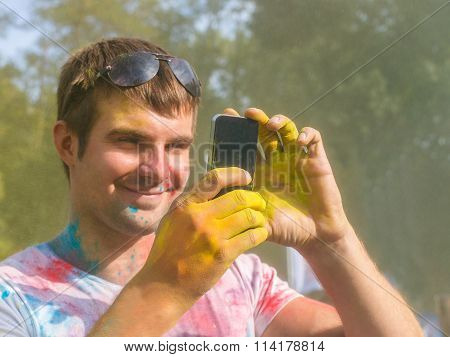Young man taking photo on mobile phone on holi color festival