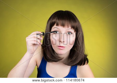 Makeup mascara woman getting ready looking in camera as in a mirror. Funny image of beautiful trendy