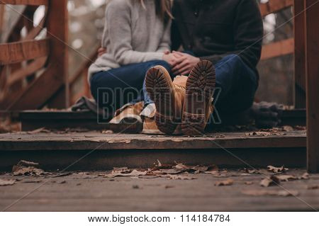 boots of young loving couple walking outdoor on wooden bridge in autumn