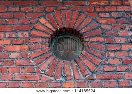 Wall of an old brick building and round window