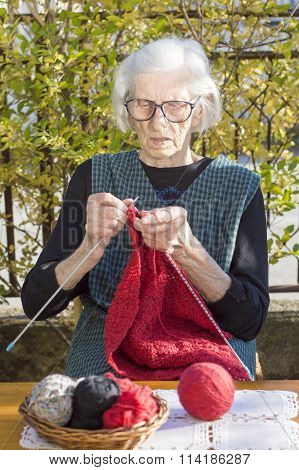 90 Years Old Woman Knitting A Red Sweater